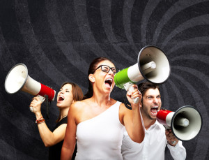 people shouting with megaphone against a grunge wall